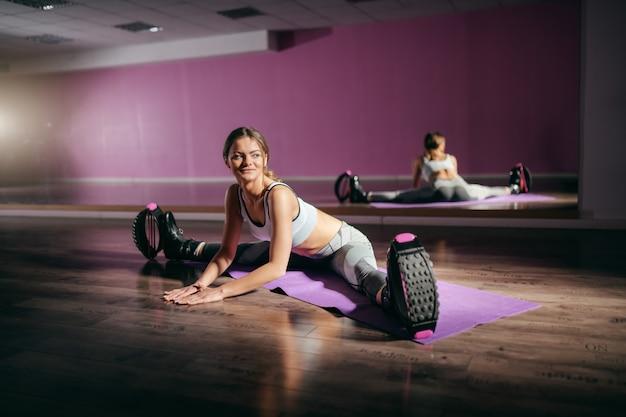 젊은 미소 백인 맞는 갈색 매트에 앉아서 캉구를 착용하는 동안 다리를 스트레칭 부츠를 점프.