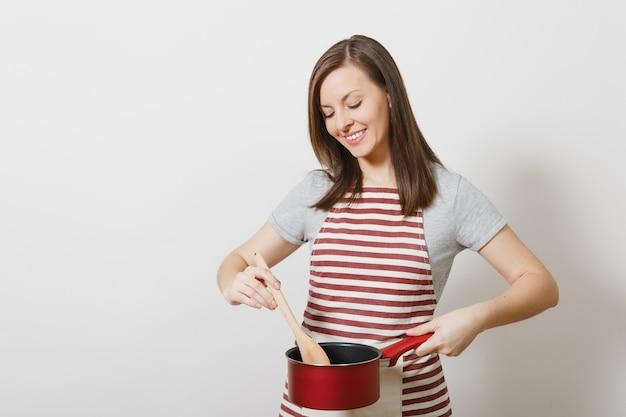 Молодая улыбающаяся кавказская домохозяйка в полосатом фартуке, серой изолированной футболке. красивая домработница женщина, держащая дегустацию красной пустой сотейник деревянной ложкой