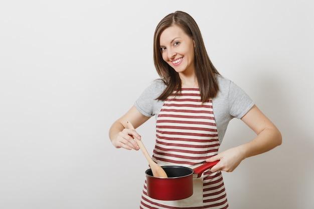 줄무늬 앞치마를 입은 젊은 백인 주부, 고립된 회색 티셔츠. 시음 빨간색 빈 스튜 냄비 나무 숟가락을 들고 아름 다운 가정부 여자 프리미엄 사진