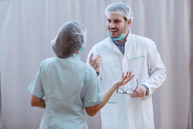 若い白い白人の男性医師の笑みを浮かべて、ヘアネットとマスクを手に眼鏡を持って、成功した手術について看護師と話し合っています。