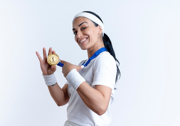 Young smiling caucasian sporty woman stands sideways holding and pointing at gold medal