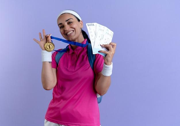 Молодая улыбающаяся кавказская спортивная женщина, носящая повязку на голову с сумкой и браслеты, держит золотую медаль и авиабилеты, изолированные на фиолетовом фоне с копией пространства