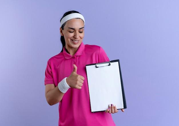 I giovani sorridenti caucasici donna sportiva indossando la fascia e braccialetti thumbs up holding appunti isolato su sfondo viola con spazio di copia