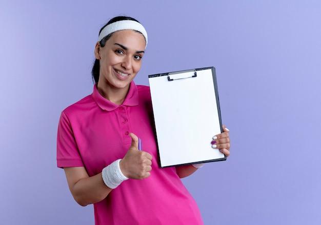 Giovane sorridente indoeuropeo donna sportiva che indossa la fascia e braccialetti pollice in alto tenendo la penna e appunti isolato su sfondo viola con spazio di copia