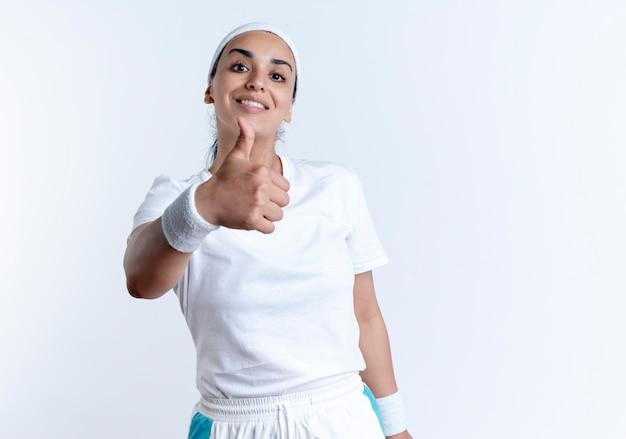 Pollici da portare della fascia e dei braccialetti da portare della giovane donna sportiva caucasica sorridente in su isolati su spazio bianco con lo spazio della copia