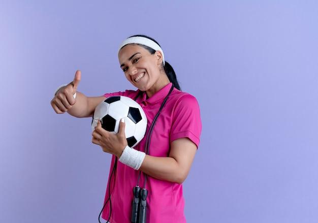 La giovane donna sportiva caucasica sorridente che indossa la fascia e i braccialetti con la corda di salto sul collo tiene i pollici della sfera in su sulla porpora con lo spazio della copia