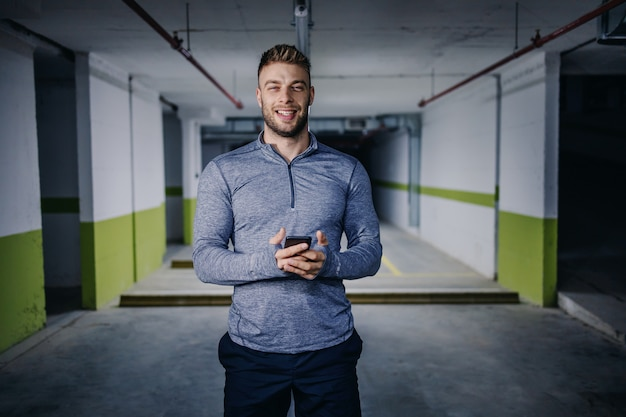 Молодой улыбающийся кавказский сильный мускулистый спортсмен в активной одежде, стоя в подземном гараже и с помощью смартфона. концепция городской жизни.