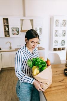 젊은 미소 백인 여자 잡고 현대 부엌에서 신선한 야채와 바게트 에코 쇼핑 가방.