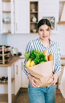 Young smiling caucasian woman hold eco shopping bag with fresh vegetables and baguette in modern kitchen.