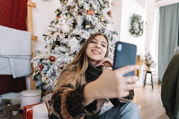 Молодая улыбающаяся кавказская женщина, делающая селфи с помощью мобильного телефона возле елки дома.
