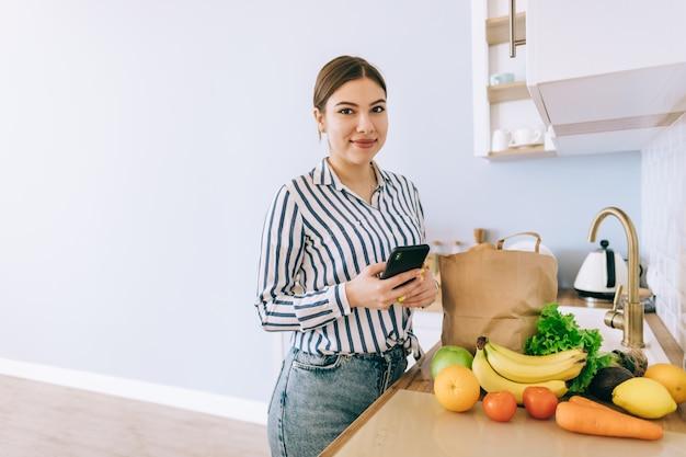 Молодая улыбающаяся кавказская женщина использует смартфон на современной кухне, сумка со свежими овощами на столе. покупка еды и продуктов в интернете.