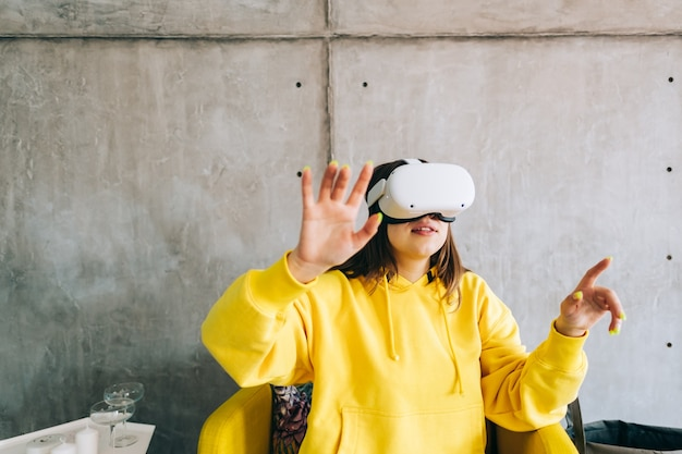 Молодая улыбающаяся кавказская женщина с помощью гарнитуры vr, жестикулируя и глядя в виртуальной реальности.