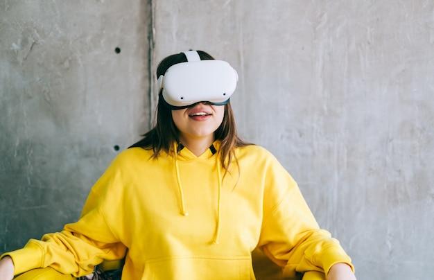 Молодая улыбающаяся кавказская женщина с помощью гарнитуры vr, глядя вверх в виртуальной реальности.