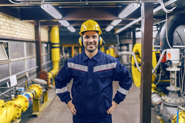 Молодой усмехаясь кавказский рабочий защитный костюм гостиницы с руками на бедрах стоя в заводе жары.