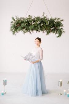 Молодой улыбающийся мастер церемонии в элегантном платье позирует под сосновым украшением перед свадебной церемонией