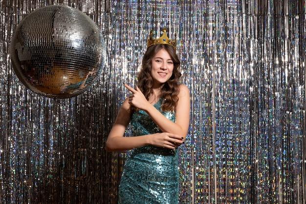 파티에서 왕관과 함께 장식 조각과 푸른 녹색 반짝이 드레스를 입고 젊은 웃는 매력적인 아가씨