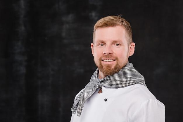 Молодой улыбающийся шеф-повар в униформе смотрит на вас, стоя на черном фоне в изоляции