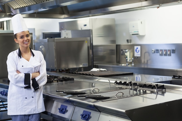 Young smiling chef standing next to work surface