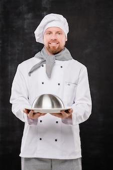 Young smiling chef in uniform holding cloche with cooked meal for you while standing in isolation against black background