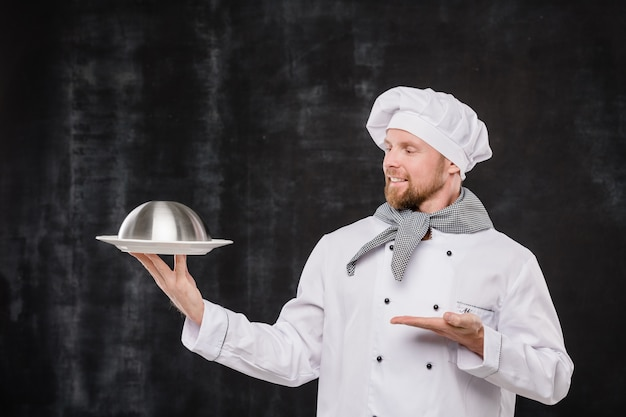 Young smiling chef in uniform looking and pointing at cloche with cooked meal while standing in isolation