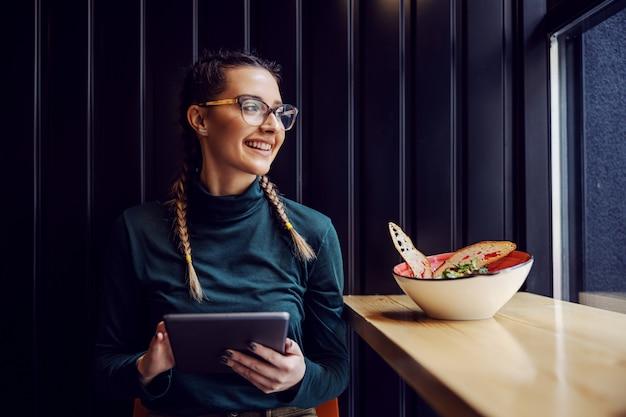 Молодая улыбающаяся девушка колледжа сидит в ресторане, держит планшет и смотрит через окно во время обеденного перерыва.
