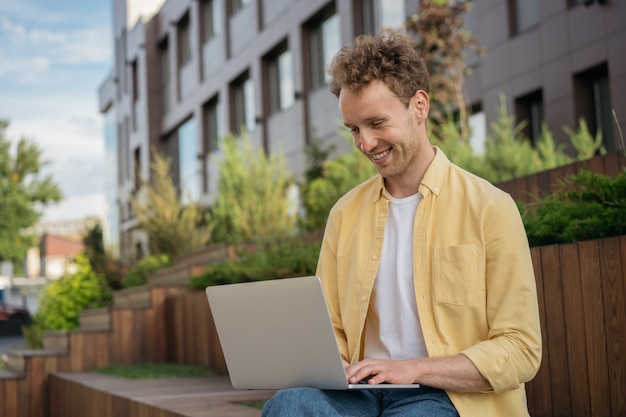 Young smiling computer programmer using laptop working freelance project online from home