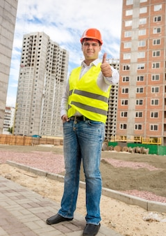 Young smiling construction engineer posing on building site with thumb up