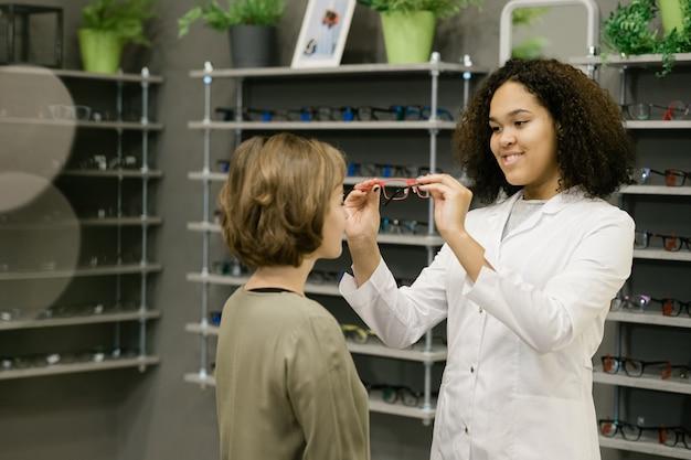 한 쌍을 시도하는 동안 클라이언트가 적합한 안경을 선택하도록 돕는 광학 상점의 젊은 웃는 컨설턴트