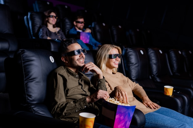 Young smiling couple in 3d eyeglasses enjoying time in cinema while sitting in armchairs in front of large screen and watching movie