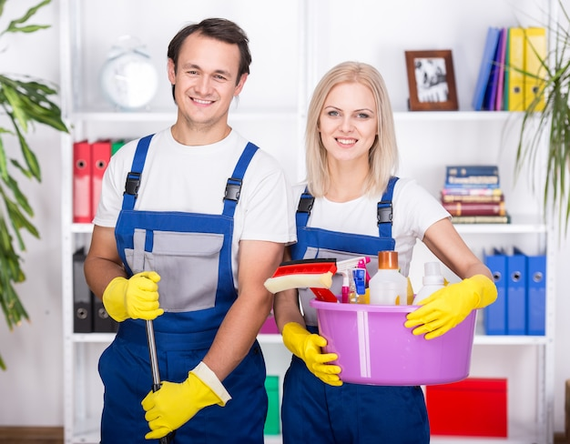 Young smiling couple are holding cleaning tools.