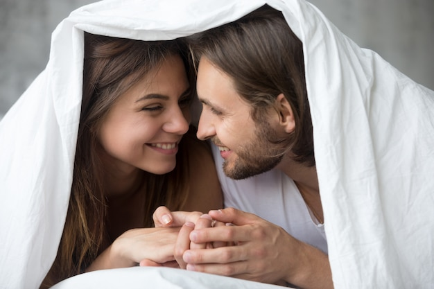 Young smiling couple in bed having fun covered with blanket