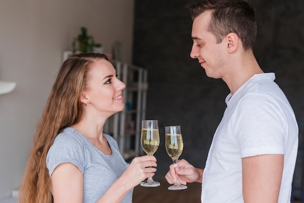 Young smiling couple clanging glasses at home