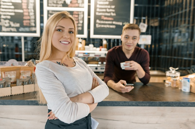 Young smiling couple of coffee shop workers