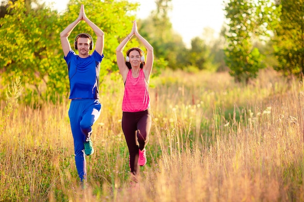 Young smiling couple doing sporty exercises outdoors