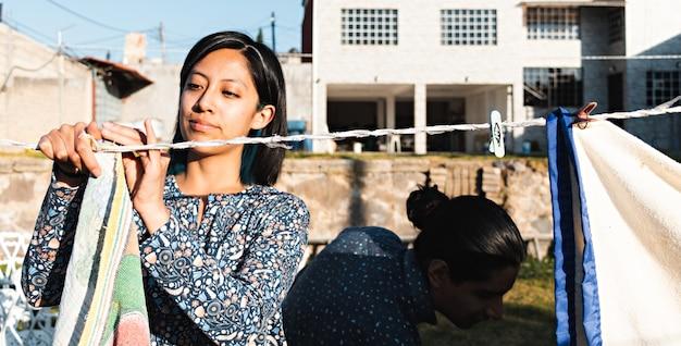 Молодая улыбающаяся пара развешивает одежду на заднем дворе