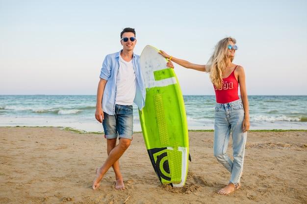 サーフボードでポーズをとってビーチで楽しんでいる若い笑顔のカップル
