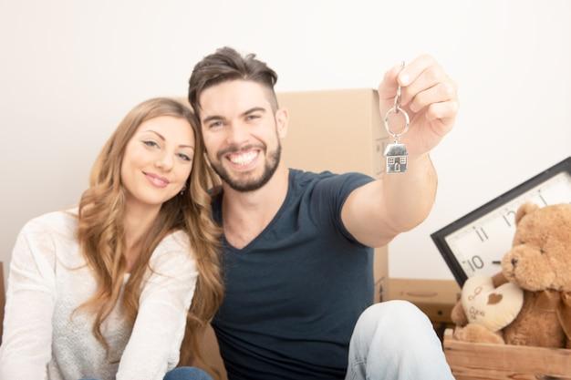 Молодая улыбающаяся пара держит ключи от нового дома, недвижимость и концепцию переезда