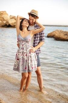 Молодая улыбающаяся влюбленная пара, стоящая на пляже и обнимающаяся