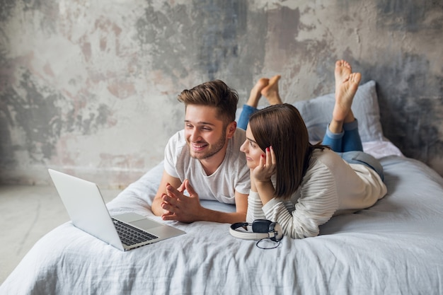 Young smiling couple lying on bed at home in casual outfit, looking in laptop, man and woman spending happy time together, relaxing