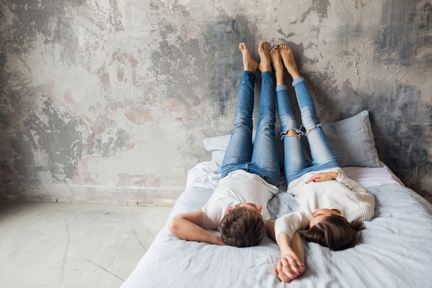 Young smiling couple lying on bed at home in casual outfit