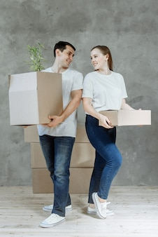 Young smiling couple man and woman in hands with boxes for moving in a new apartment.