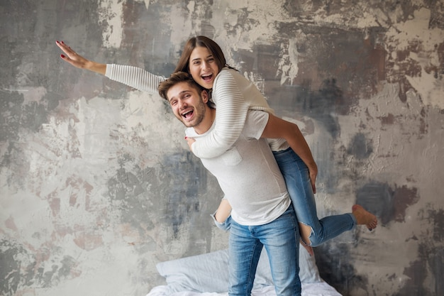 Young smiling couple playing on bed at home in casual outfit, man and woman having fun together, crazy positive emotion, happy, holding hand up