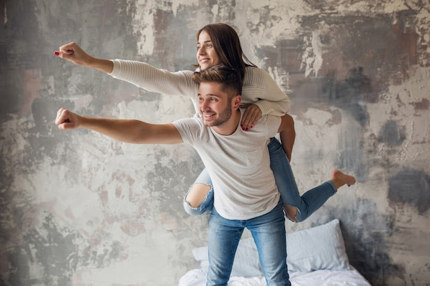 Молодая улыбающаяся пара играет на кровати дома в повседневной одежде, мужчина и женщина веселятся вместе, сумасшедшие положительные эмоции, счастливы, держась за руку