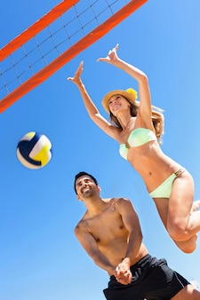 Young smiling couple playing volleyball