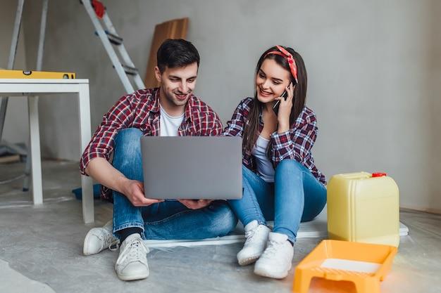 Молодая улыбающаяся пара ремонтирует и переделывает свою новую квартиру, мужчина красит стены валиком, а женщина подключается к ноутбуку