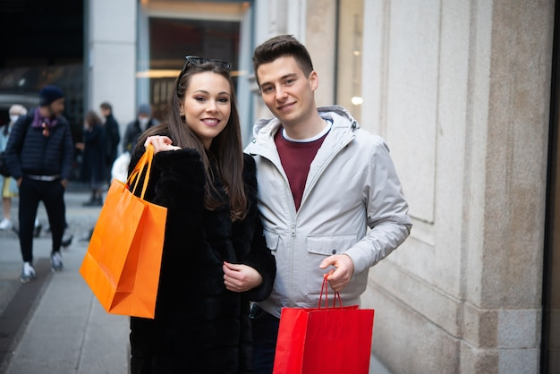 Молодая улыбающаяся пара, делающая покупки на городской улице