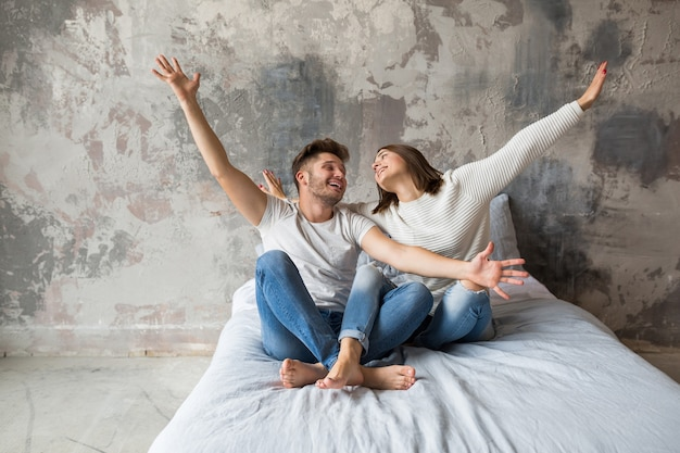 Young smiling couple sitting on bed at home in casual outfit, man and woman having fun together, crazy positive emotion, happy, holding hands up