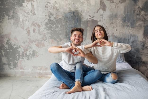 Giovane coppia sorridente seduto sul letto a casa in abbigliamento casual, uomo e donna divertendosi insieme, folle emozione positiva, felice, mostrando il segno del cuore
