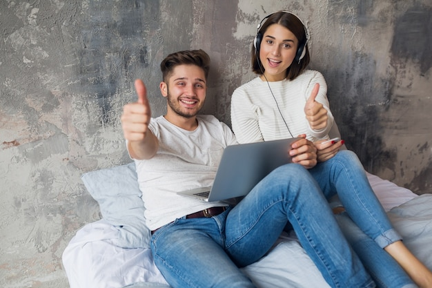 Young smiling couple sitting on bed at home in casual outfit, man working freelance on laptop, woman listening to music on headphones, spending happy time together, positive emotion, looking in camera