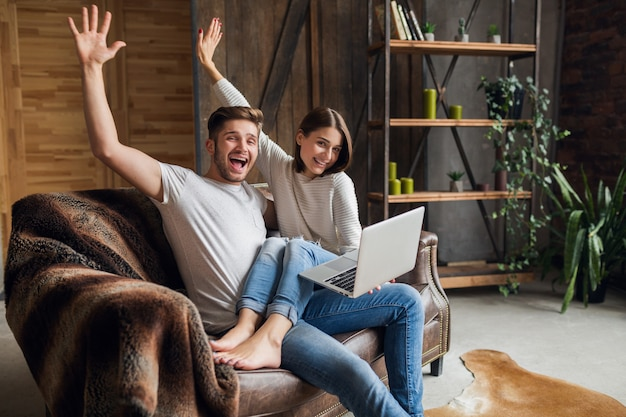 Young smiling couple sitting on couch at home in casual outfit, love and romance, woman and man embracing, wearing jeans, spending relaxing time together, holding laptop, happy emotional